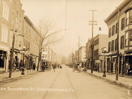 Looking North on South Main Street towards the intersection of East Queen and South Main Streets in 1914.  The building on the right with an X is where Edward Metz's business was located.