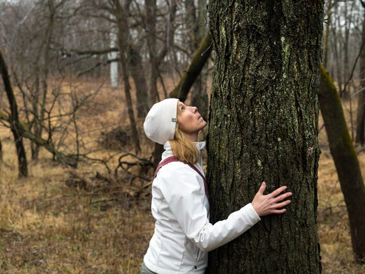 Dr. Suzanne Bartlett Hackenmiller hugs a tree as she