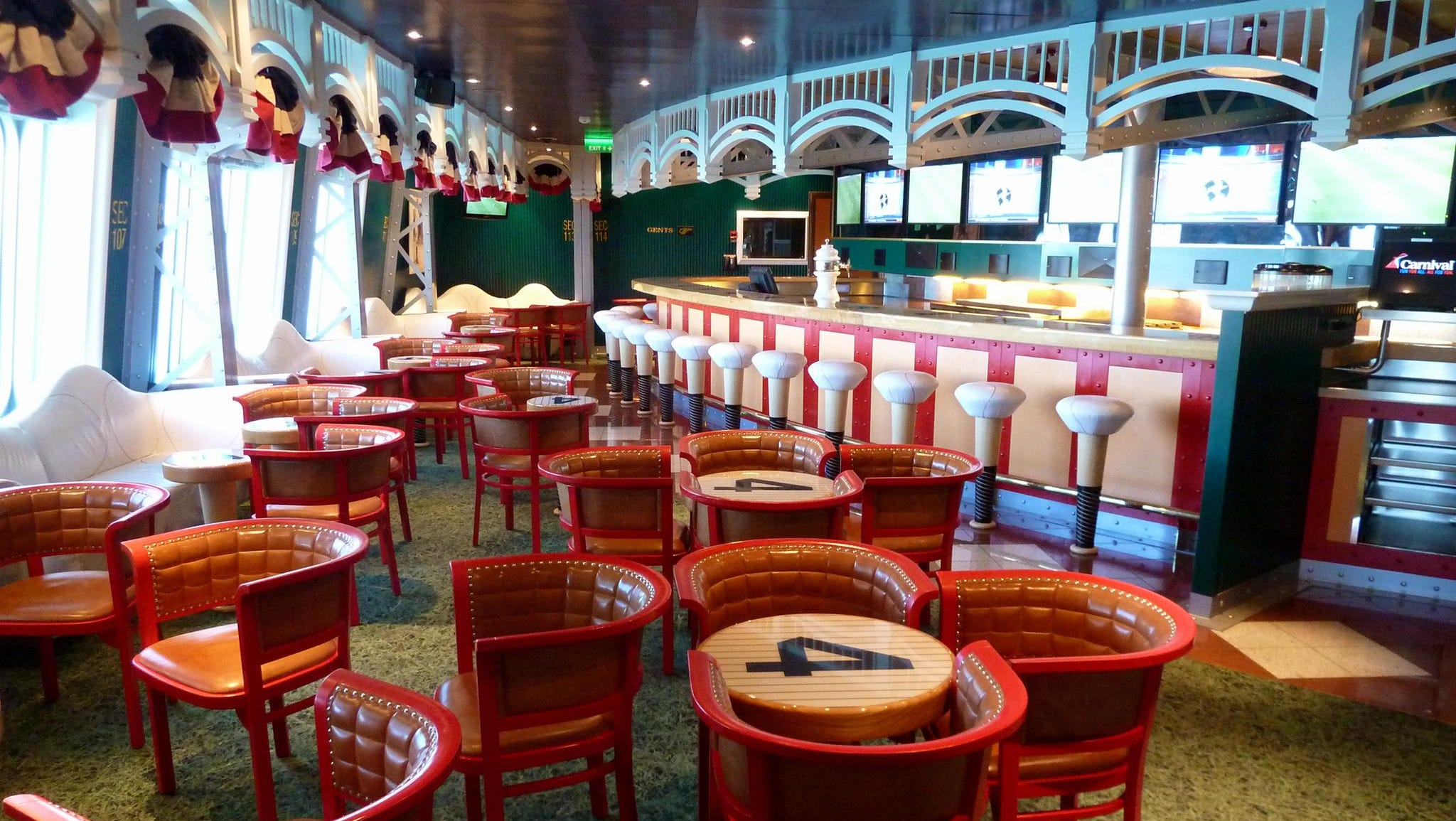 "The Bronx Bar is a 55-seat sports bar on the port side of Deck 5. Decor is dedicated to the Yankees and famed ""number four,"" Lou Gehrig. Banquettes are styled after baseballs, bar stools resemble sawed off bats and the carpet is the color of grass."