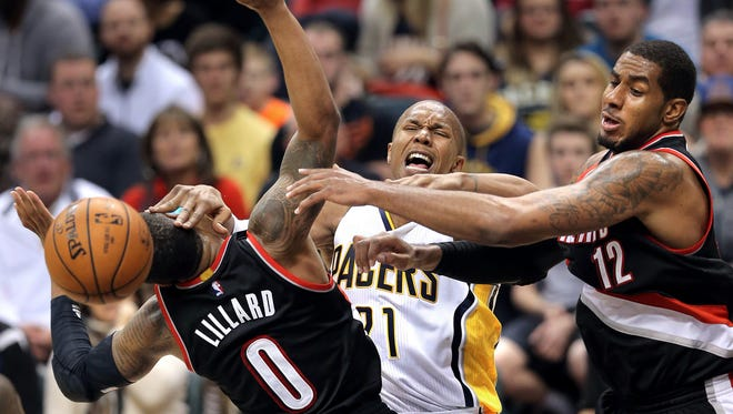 Pacers forward David West gets tangled with Portland players Damian Lillard, left, and LaMarcus Aldridge, Dec. 13, 2014.