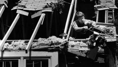 AUGUST 2, 1980: Roofless: Mark Huesman of Martz Builders begins the task Friday, 8/1/80, of repairing the roof at the home of Kathy Luby, 5791 Beechgrove, Western Hills. The roof was damaged when a storm which swept through the Tristate area early Friday uprooted a tree in her backyard and sent it crashing onto the house.