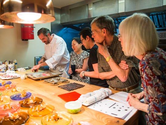 Guests watch chef Kevin Binkley prepare bluefin tuna