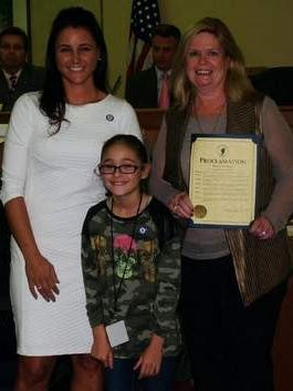 Mayor Stephanie Murray, Mayor for A Day Chloe Davis and Social Services Director during a presentation for Make A Difference Day
