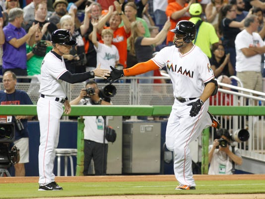 Miami Marlins' Giancarlo Stanton, right, is congratulated by third base coach Brett Butler, left, after hitting a third-inning solo home run against the Atlanta Braves during a baseball game in Miami, Friday, May 15, 2015. (AP Photo/Joe Skipper)