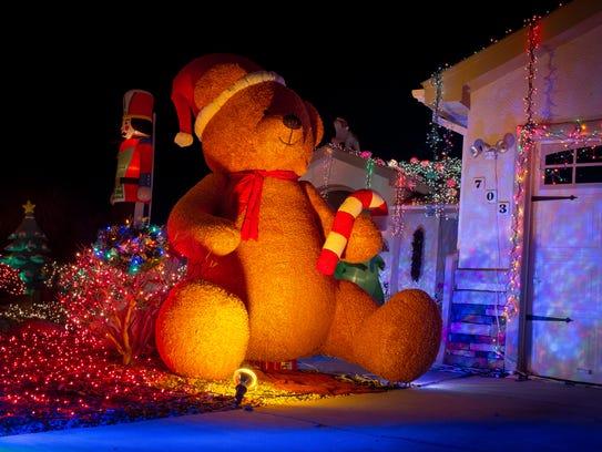 A massive Christmas-themed inflatable teddy bear holds