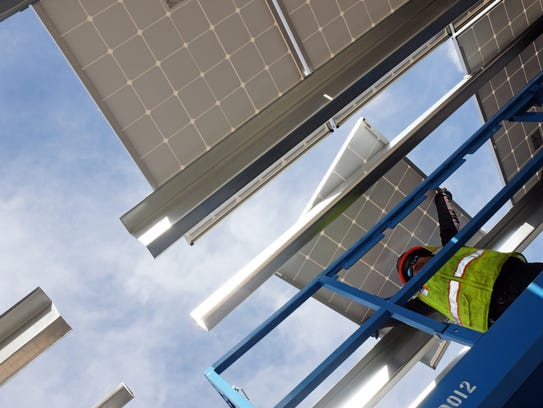 Salvador Yepis of MBL-Energy fits solar panels into