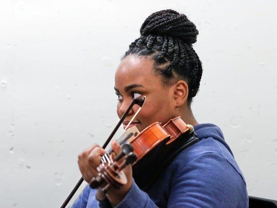 Gileisha Walker, 17, a violin student at SCPA, listens