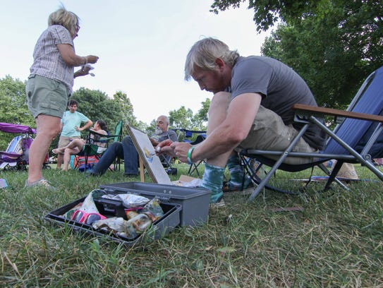Matt Sipe paints while waiting for a evening concert