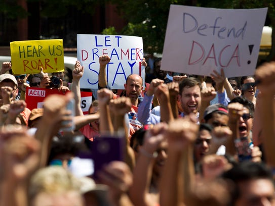 Protesters hold up signs during a rally supporting