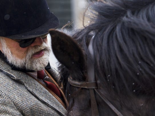 Joe Patteson adjusts the bridle on his horse, Schuster,