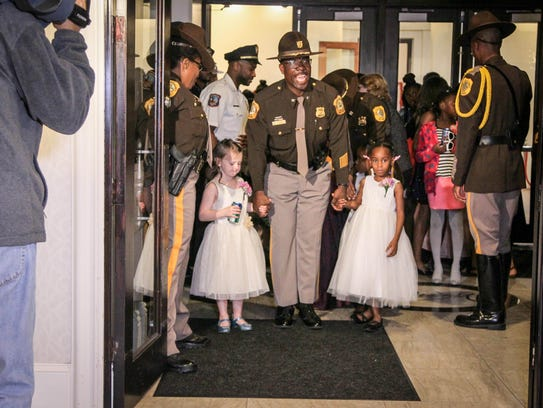 Col. Vaughn Bond, chief of the New Castle Police Department, escorts two girls into the first Police and Princess Ball on Friday, Oct. 13, 2017, at the Waterfall Banquet and Conference Center in Claymont.