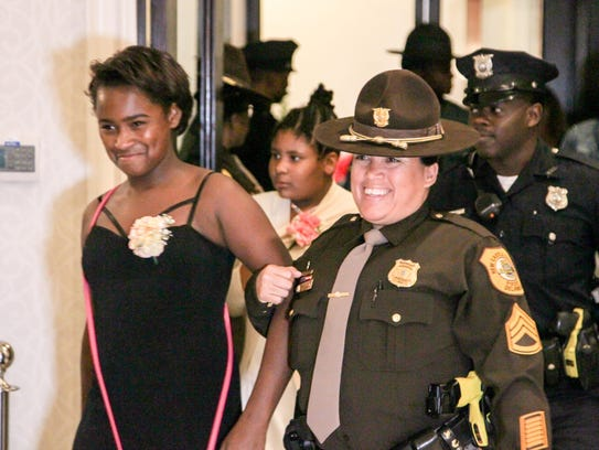 A New Castle County police officer escorts a girl into the inaugural Police and Princess Ball on Friday, Oct. 13, 2017, at the Waterfall Banquet and Conference Center in Claymont.