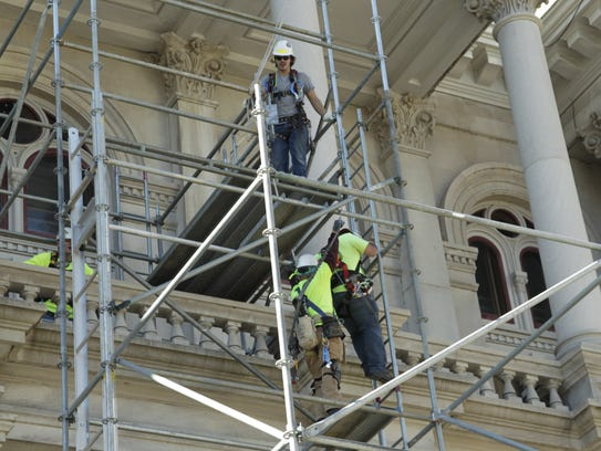 Construction workers remove scaffolding Nov. 28, 2017,