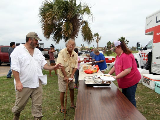 After Hurricane Harvey, about 40 residents of Rising Star, population 700, went hog hunting, then traveled 400 miles with smoked pork to feed thousands of residents in Port Aransas and Rockport. Here, organizer Scott Hayley encourages hurricane victims to eat up.