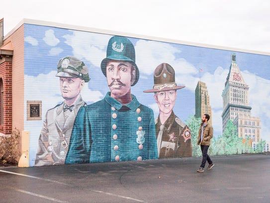 Wyatt Cenac walks by a mural in Cincinnati, one of