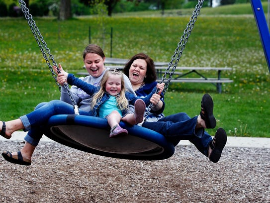Kolbe Kawleski (center), 4,  shares a swing ride with