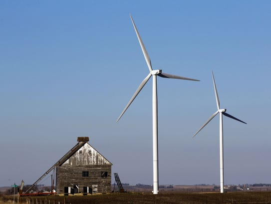 A pair of wind turbines tower over a barn at a wind