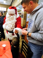 Jacob Sledge, 2, gives a high-five to Santa as his father, Jake, looks on during the 2015 Breakfast with Santa event at the Mall of Abilene.