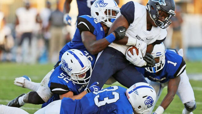Wesley football's Bryce Shade is tackled by four CNU defenders. The Wolverines lost 42-28 to the Captains on Saturday