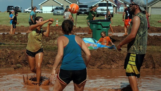 Teams compete in the Pig Pen Mud Volleyball Charity Tournament at the Iowa Park Fourth of July celebration at Gordon Lake.