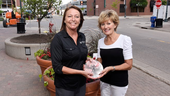 St. Cloud Federal Credit Union COO Alyce Justin presents St. Cloud Downtown Council volunteer Penny White with a ChangeMaker award Tuesday, June 7, in St. Cloud.