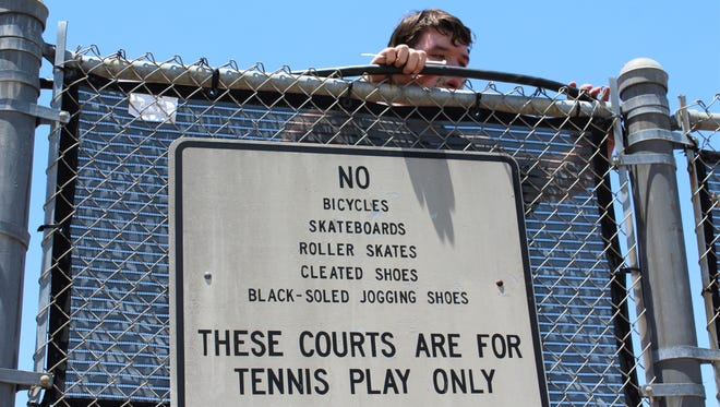 Collin Gardner, of Wyatt Electrical Services, helps install a temporary electrical panel at a court at the Rose Park Tennis Center on Wednesday. The work projects is part of preparations for The Texas Slam, a juniors tournament that begins play Saturday.