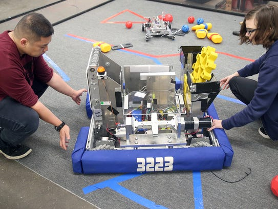Central Kitsap High School robotics team students Michael Frilles, left, and Lauren Judd work on the device used in last year's competition. A different robot, already shipped to Houston, was used by this year's team.