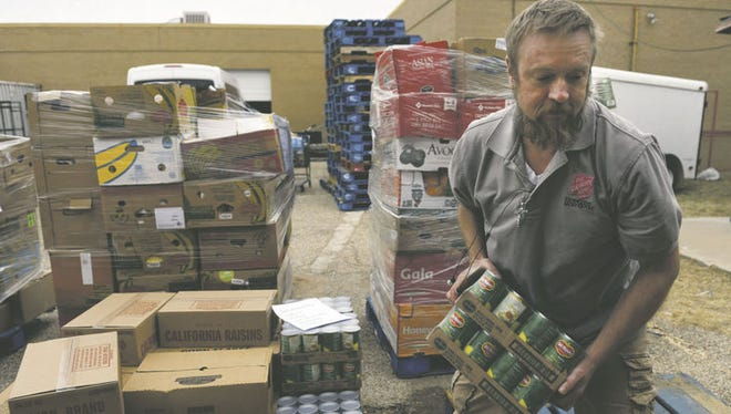 Chris Cooper, Salvation Army Shelter manager, moves items delivered by the West Texas Food Bank to the shelter recently.