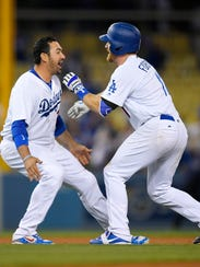 Adrian Gonzalez, left, celebrates with Logan Forsythe after Forsythe's walk-off RBI double to beat the St. Louis Cardinals in 13 innings on May 23, 2017. (AP Photo/Mark J. Terrill)