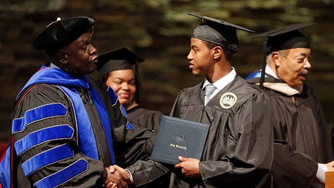 Krishaun Branch receives his diploma from Harvard Law School professor Charles Ogletree Jr., during the graduation ceremony for Fisk University in Nashville.