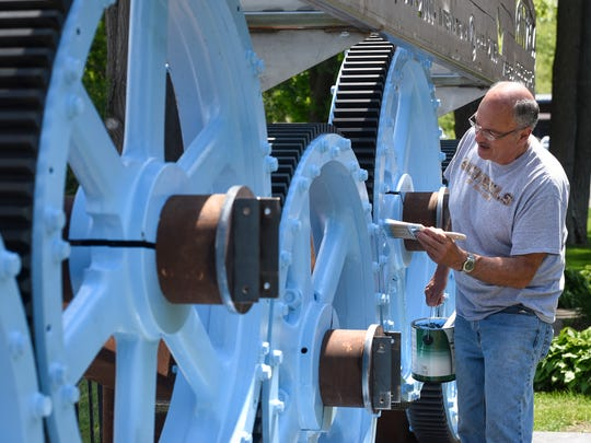 Dennis Mollitor does some touch-up work to a monument honoring the paper mill in Sartell Friday, May 26, shortly after it was installed.