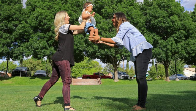 Chelsea Judd plays with her daughter, Giselle, and Tia Stokes, on May 2 at Nisson Park in Washington City. When Chelsea faced fertility issues, Tia donated eggs for in vitro fertilization.