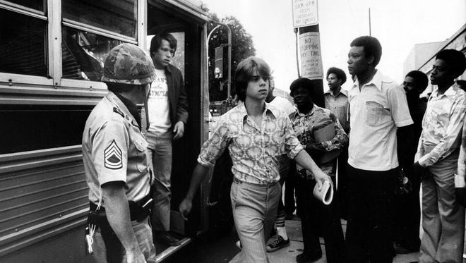 Students from Jeffersontown High School unload as Central students wait to reload a bus.  1975
