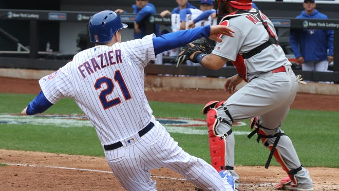 Todd Frazier slides into home scoring a fifth inning run for the Mets. Cardinals catcher Yadier Molina got the throw too late.