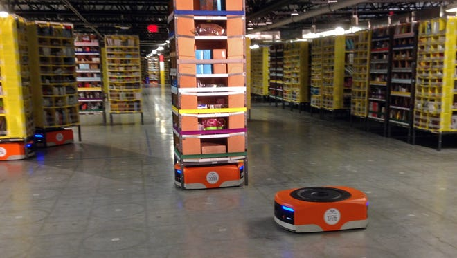 A Kiva robot moves under a stack of merchandise during a tour of one of Amazon's newest distribution centers in Tracy, Calif., on Nov. 30, 2014.