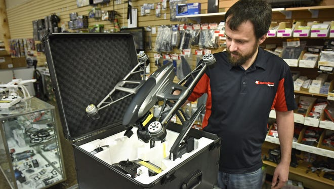 Baker's HobbyTown manager Jason Wester unpacks a drone in October 2015 at the Waite Park store.