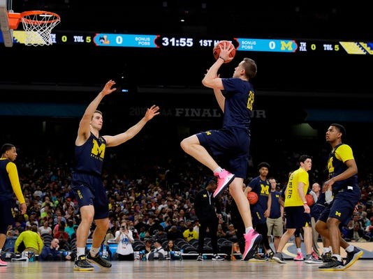 Michigan's Duncan Robinson (22) shoots during a practice session for the Final Four NCAA college basketball tournament, Friday, March 30, 2018, in San Antonio. (AP Photo/David J. Phillip)
