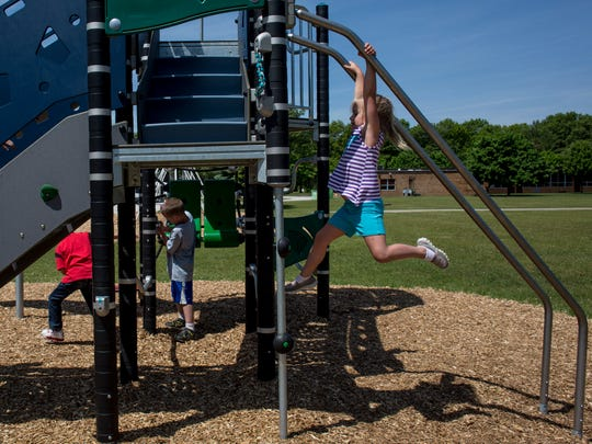 Kindergarten student Karena Harris, 6, climbs up on new playground equipment Tuesday, May 31, 2016 at Crull Elementary School in Port Huron. The Crull PTA raised $15,000 over three years, and received a $15,000 match from a local business to pay for the equipment.