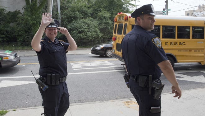 "Police officers Mary Gillespie, left, of the 120th precinct on Staten Island borough of New York, waves at a residents of the Richmond Terrace Houses while on patrol with fellow officer Jessi D'Ambrosio on Thursday, July 7, 2016. In 2015, the city began assigning pairs of officers to specific neighborhoods, rather than having them rush from call to call across precincts. They are mandated to spend a third of their shift ""off-radio,"" talking with residents to forge relationships. The new approach was rolled out to the North Shore in December. (AP Photo/Mary Altaffer)"