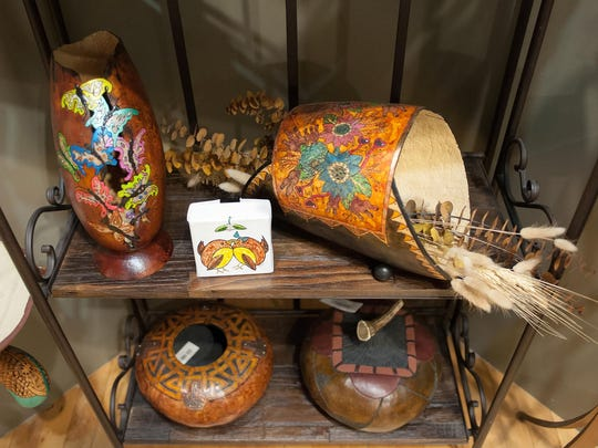 """In a photo from June 13, 2015, some of Doug Wolff's artistic gourds and paintings are displayed at the EastEnd Studio and Gallery in downtown Marshall, Mich. Since his retirement as director of Dam Site Design, a design consultant firm in Ceresco, Wolff has found art, both as an acrylic painter and, perhaps most noteworthy, as a gourd carver. His exhibition is titled ?The Wonders of Wolff."""" (Seth Graves/Battle Creek Enquirer via AP)"""