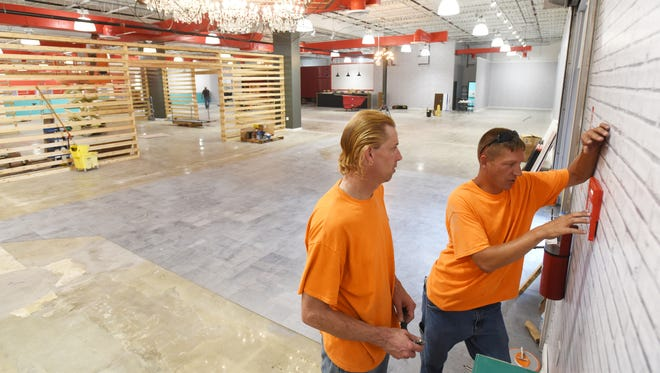 Sam Layne, right, and Brandon Miller of StarTec Security work on the security system at the new Big Sandy Superstore in Zanesville.