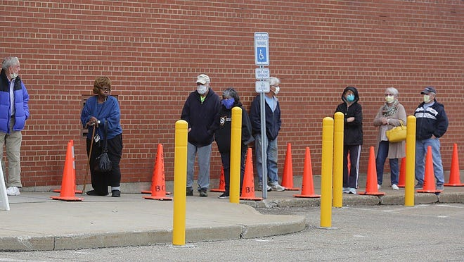 People wearing masks wait in line outside the Stark County Board of Elections in Canton to cast their ballots in the primary on April 28.