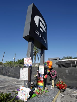 FILE - In this June 22, 2016 file photo, a makeshift memorial is seen at the base of the sign of the Pulse nightclub, scene of the recent mass shooting, in Orlando.  (AP Photo/John Raoux, File)