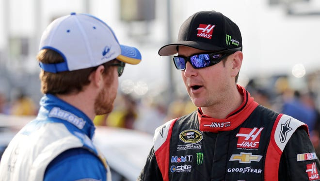 Kurt Busch, right, talks with Brian Vickers, left, before qualifying for a NASCAR Sprint Cup series auto race at Darlington Speedway in Darlington, S.C., April 11, 2014.