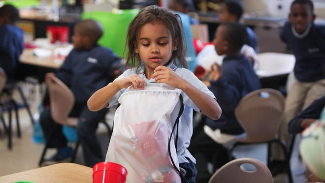 "Masarah Chambers, 6, takes a look inside her ""blessing bag"" on Friday."