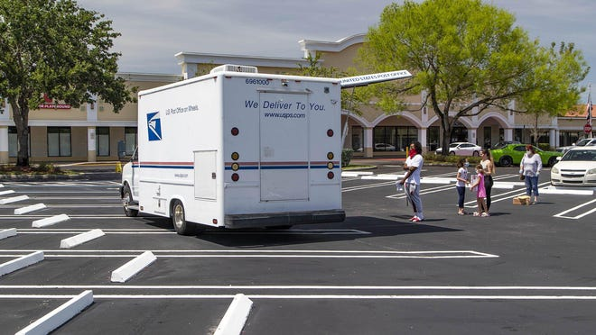 A mobile U.S. Post Office truck sits in the parking lot outside the Post Office on Southern Boulevard in Royal Palm Beach to relieve crowded conditions inside, and to allow more social distancing due to the coronavirus outbreak.