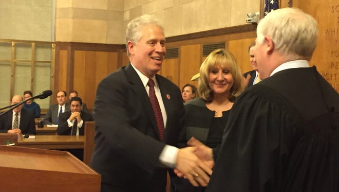 Westchester Legislator Michael Kaplowitz shakes the hand of Administrative Judge Alan Scheinkman after taking his oath of office on Jan. 4, 2016. The Legislature chairman is joined at the podium by his wife, Jayne.