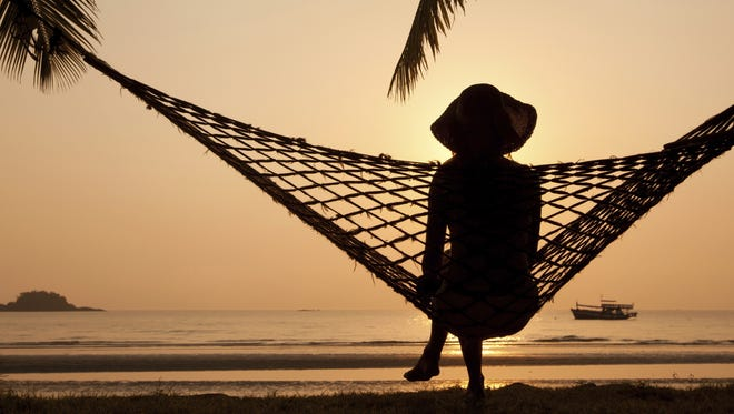 A silhouette of a woman in a hammock.