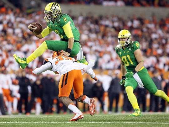 Marcus Mariota hurdles Justin Strong during the annual Civil War college football battle between Oregon and Oregon State at Reser Stadium in Corvallis.