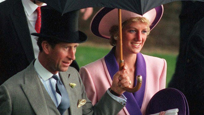 In this June 20, 1990, file photo, Britain's Princess Diana and Prince Charles take shelter under an umbrella while attending the second day of the Royal Ascot horse race near London.